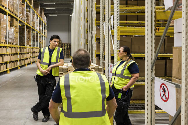 Travailleurs multi-ethniques discutant tout en se tenant près des rayonnages à l'entrepôt de distribution — Photo de stock
