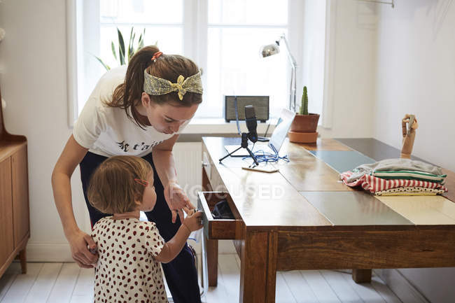Podcaster looking at daughter opening drawer while standing by table — Stock Photo