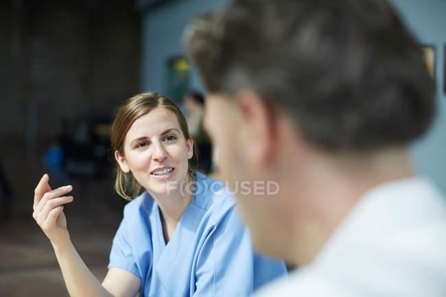 Enfermera femenina sonriente discutiendo con un médico maduro mientras está sentada en la cafetería en el hospital - foto de stock
