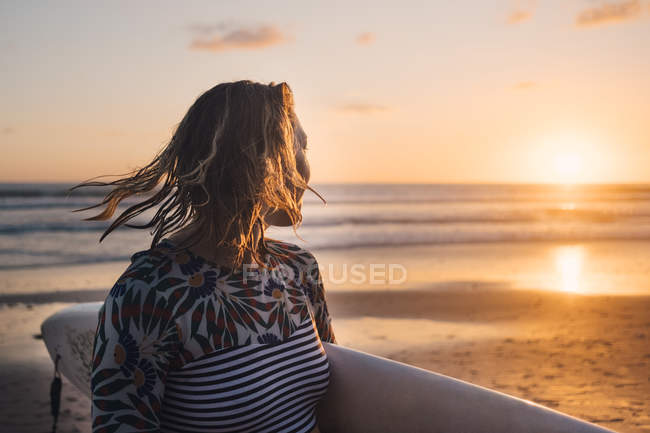 Female surfer with surfboard looking at sea during sunset at beach — Stock Photo