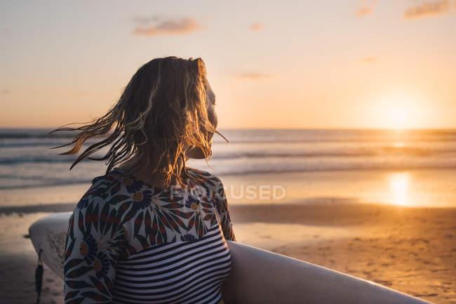 Surfista donna con tavola da surf che guarda il mare durante il tramonto in spiaggia — Foto stock
