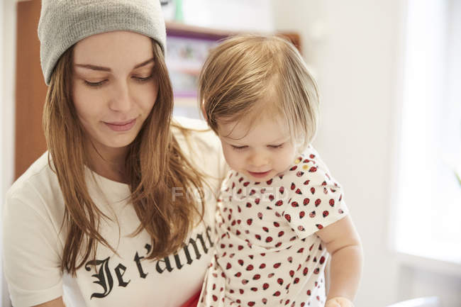 Mother carrying daughter while looking down at home — Stock Photo
