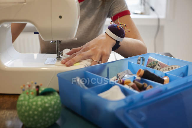 Midsection of tailor using sewing machine by blue box at table — Stock Photo