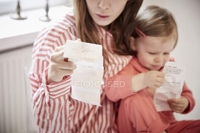 Mother and daughter with financial bills at home — Stock Photo