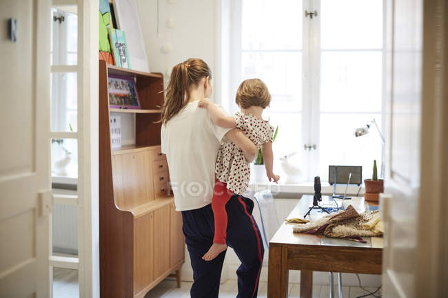 Female influencer carrying daughter while standing by table at home — Stock Photo