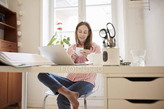 Full length of young woman examining financial bill while working from home — Stock Photo