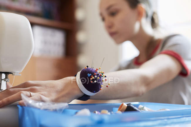 Close up of female tailor wearing pin cushion on wrist while using sewing machine at table — Stock Photo