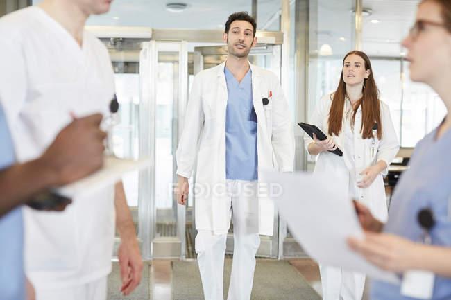 Equipo de atención médica multiétnica discutiendo en el lobby en el hospital - foto de stock