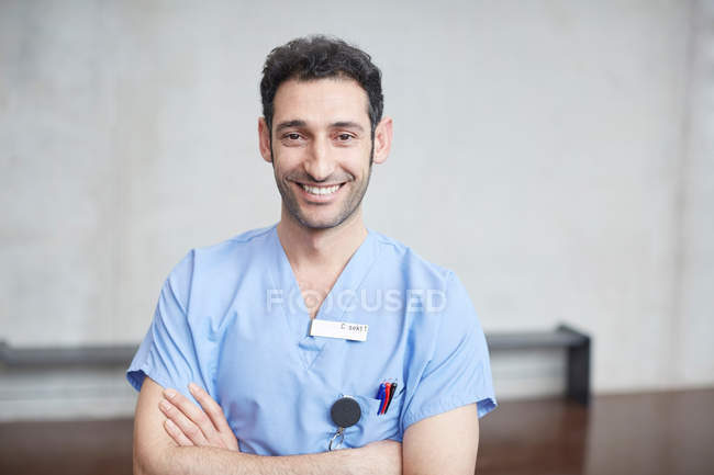 O retrato da enfermeira masculina nova de sorriso no azul esfrega a posição com os braços cruzados de encontro à parede no hospital — Fotografia de Stock