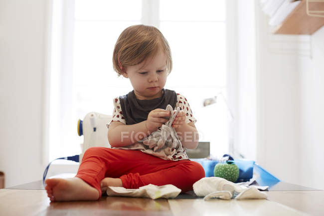 Full length of girl playing while sitting on table at home — Stock Photo