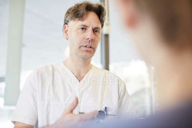 Mature male nurse discussing with female coworker at lobby in hospital — Stock Photo