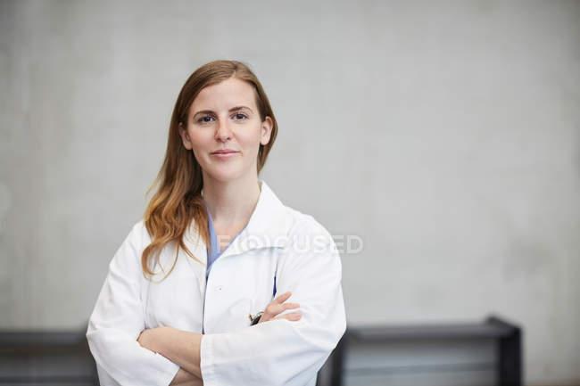 Retrato do doutor fêmea adulto meados de confiável que está com os braços cruzados de encontro à parede no hospital — Fotografia de Stock
