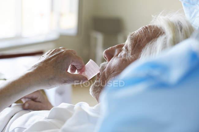 Visão lateral do paciente sênior do sexo masculino em uso de xarope de tosse em enfermaria hospitalar — Fotografia de Stock