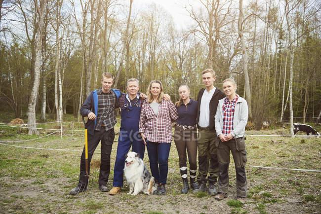 Full length of farmer with family standing on field against trees — Stockfoto