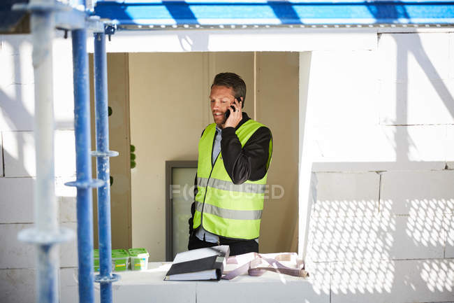 Architect talking on mobile phone while standing at incomplete building — Stockfoto