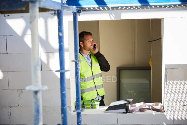 Male architect talking on mobile phone while standing at incomplete building — Stockfoto