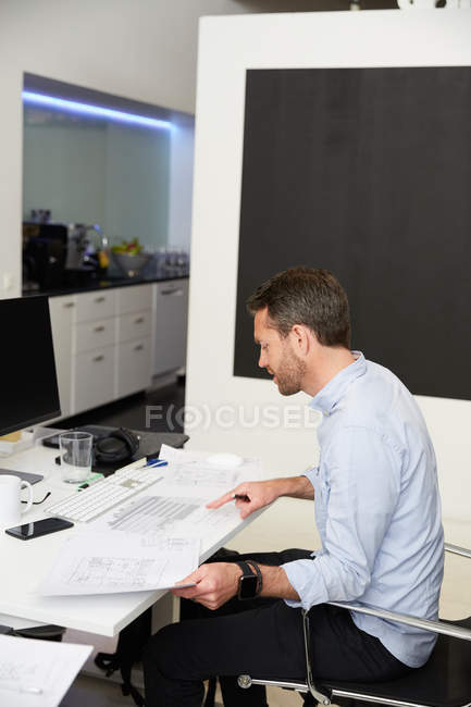 Side view of architect analyzing blueprints at desk in creative office — Stock Photo