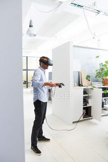 Uomo d'affari che utilizza il simulatore di realtà virtuale mentre si trova in ufficio creativo — Foto stock