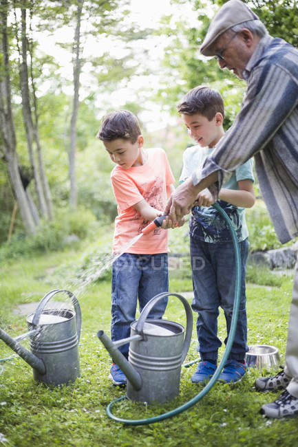 Grandfather with grandsons holding garden hose while filling watering cans in back yard — Stock Photo