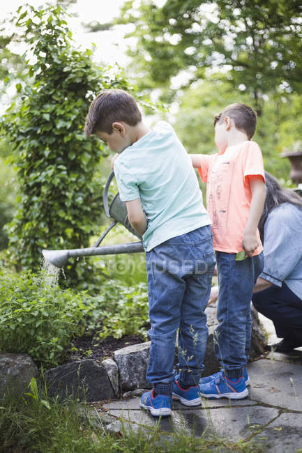 Boys watering plants by grandmother in back yard — Photo de stock
