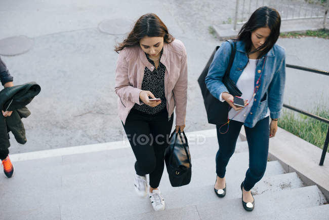 High angle view of female friends moving up on staircase while using smart phones — Stock Photo