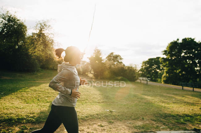 Side view of female athlete jogging at park during sunny day — Stock Photo