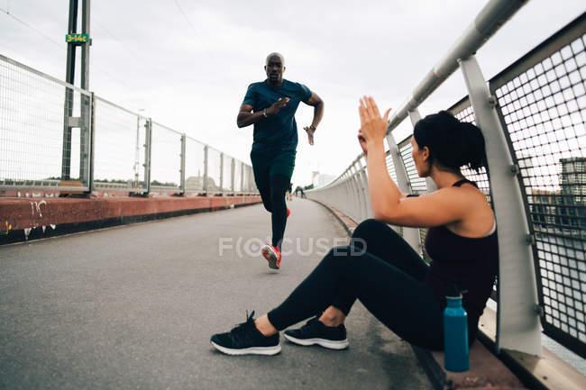 Sportswoman cheering male athlete running on footbridge in city — Stock Photo