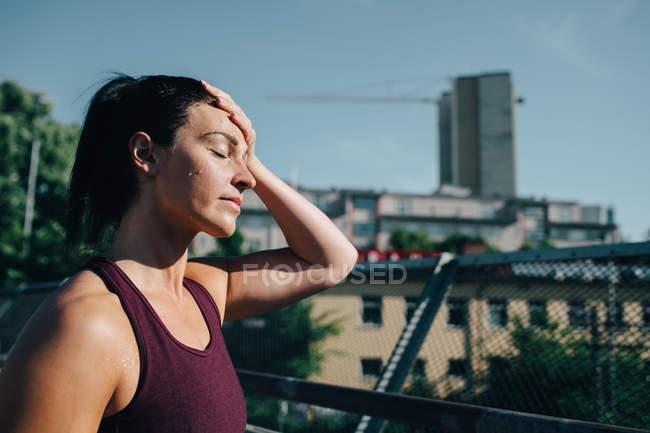 Erschöpfte Sportlerin wischt sich bei sonnigem Tag Schweiß von der Stirn — Stockfoto