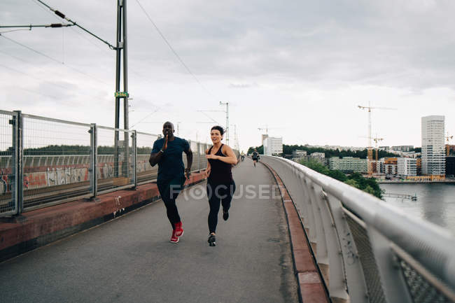 Full length of male and female athletes running on footbridge in city — Stock Photo