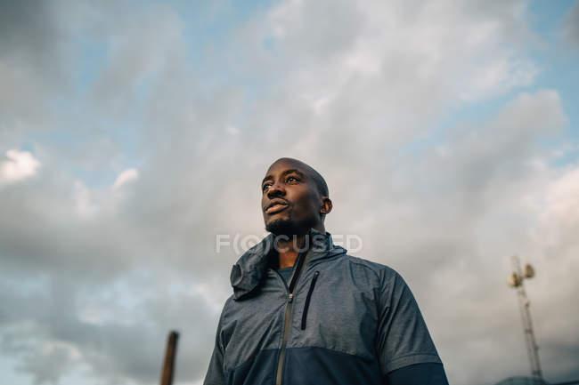 Visão de baixo ângulo do atleta masculino olhando para longe enquanto estava contra o céu nublado — Fotografia de Stock