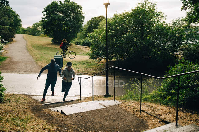 Male and female athletes running towards steps on hill — Stock Photo