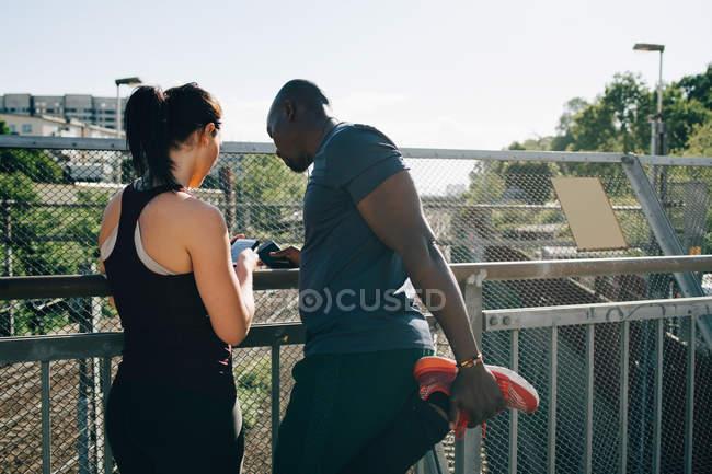 Спортсменка, показывая мобильный телефон человека, растяжение ноги, перила на мосту — стоковое фото