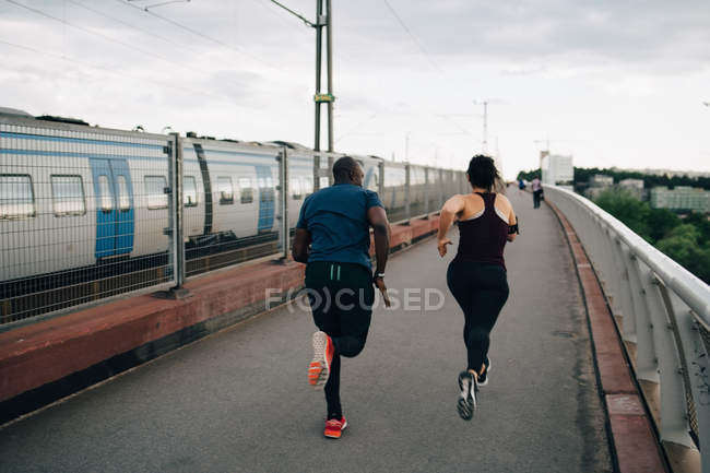 Rear view of male and female athletes running on footbridge in city — Stock Photo