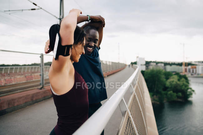 Smiling male and female athletes stretching hands on footbridge over sea against sky — Stock Photo
