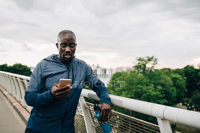 Deportista usando teléfono móvil mientras se apoya en barandilla en la pasarela contra el cielo - foto de stock