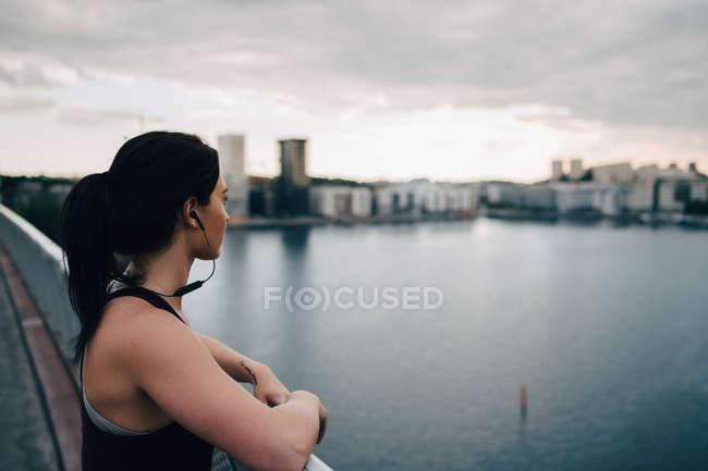Вид сбоку спортсменки, смотрящей на город, стоя на пешеходном мосту над морем — стоковое фото