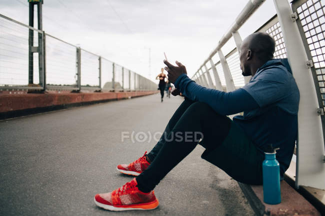 Sportsman holding mobile phone while looking at female athlete running on footbridge — Stock Photo