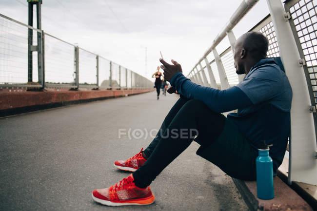 Спортсмен, удерживая глядя на спортсменка, работающие на мостках мобильного телефона — стоковое фото