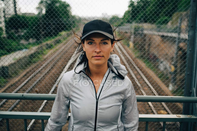 Retrato de atleta feminina confiante em pé contra trilhos na ponte — Fotografia de Stock