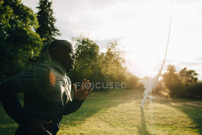 Side view of male athlete jogging at park during sunny day — Stock Photo
