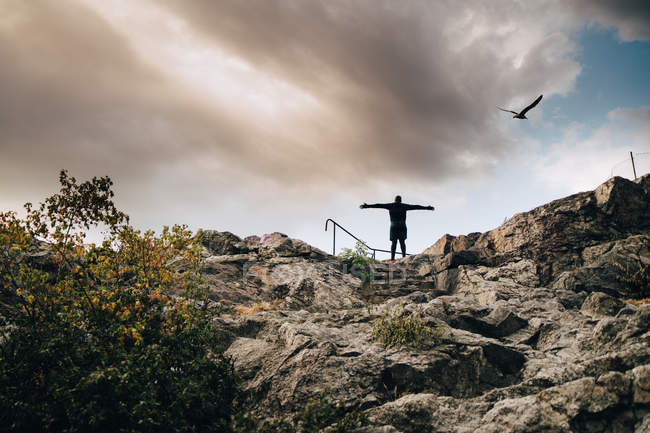 Низким углом зрения мыжского спортсмена, стоя с оружием протянутой на холме против неба. — стоковое фото