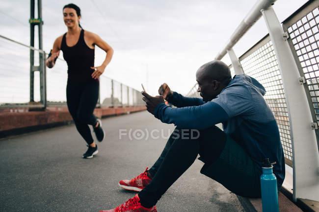 Sportsman holding mobile phone while cheering female athlete running on footbridge — Stock Photo