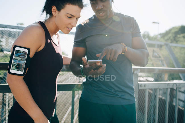 Sportsman showing mobile phone to female athlete while standing by railing on bridge — Stock Photo
