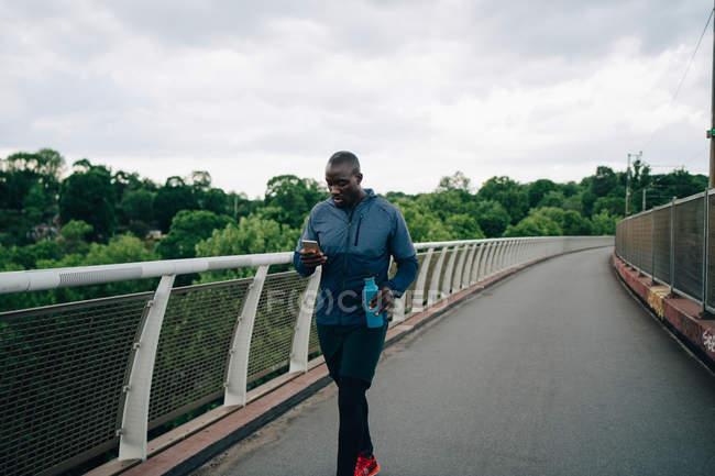 Atleta masculino usando telefone celular enquanto caminhava na passarela contra o céu na cidade — Fotografia de Stock