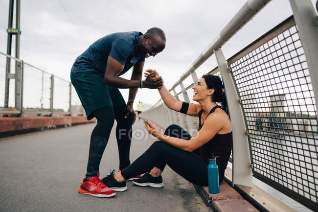 Веселий чоловік і жінка спортсменів, тримаючись за руки під час спортивної підготовки на місток — стокове фото