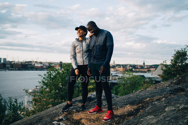 Full length of happy male and female athlete standing on hill against sky — Stock Photo