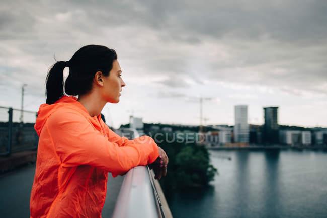 Vista lateral de la atleta femenina en impermeable mirando hacia otro lado mientras está de pie en la pasarela sobre el mar - foto de stock