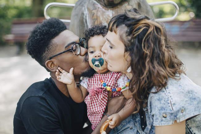 Madre y padre besando hija chupando chupete en patio de recreo - foto de stock