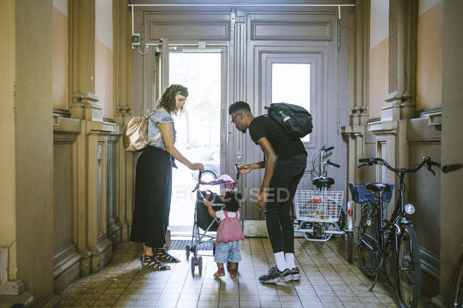Mother and father looking at daughter pushing baby stroller in corridor of apartment — Stock Photo