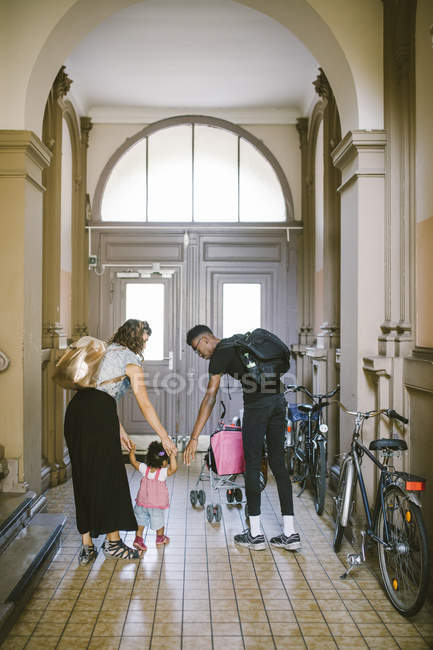Full length of mother and father assisting daughter in walking at corridor — Stock Photo